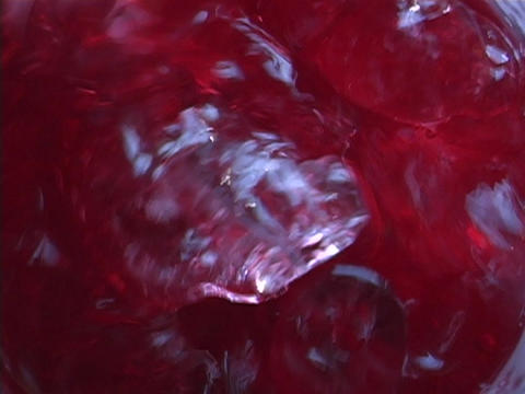 Ice blends with a ruby red liquid Stock Video Footage