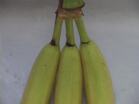 Three bananas sit on a flat surface Stock Video Footage