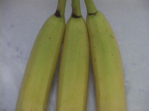 Three bananas sit on a flat surface Footage