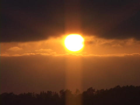 A bright orange sun appears between purple clouds Stock Video Footage
