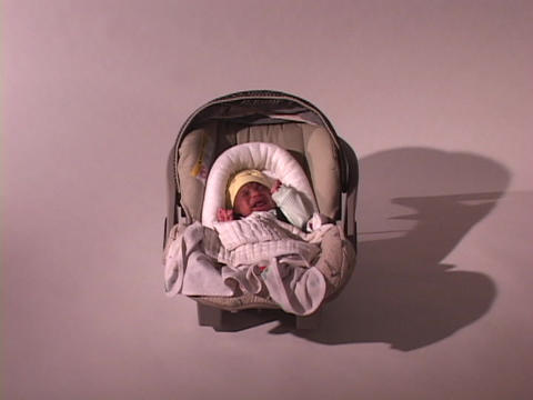 A baby lies in a car seat and cries Stock Video Footage