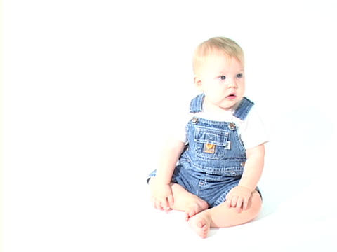 A baby boy in jean overalls sits in a white room Stock Video Footage