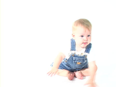 A baby boy in jean overalls sits in a white room Footage