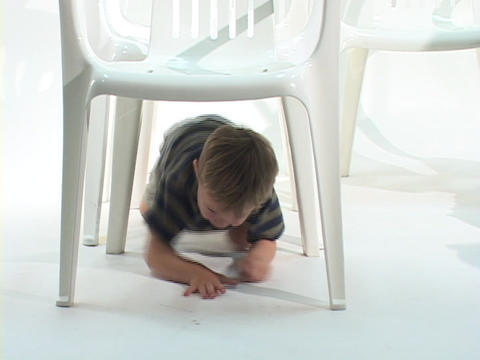 Children crawl underneath white chairs Stock Video Footage