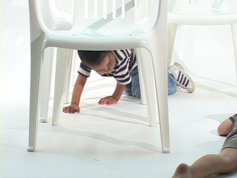 Children crawl underneath white chairs Live Action