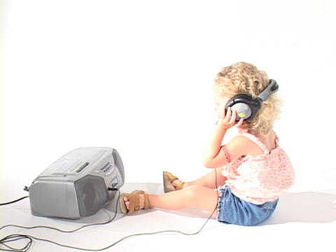 A little girl puts on headphones to listen to a boom box Stock Video Footage