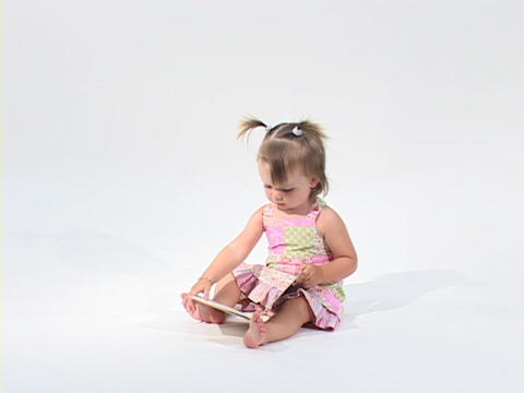 A little girl reads a book while sitting in a white room Stock Video Footage