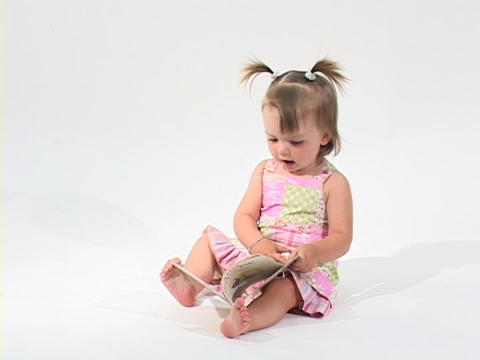 A little girl reads a book while sitting in a white room Footage