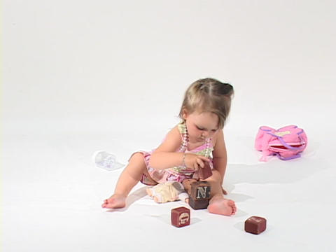A little girl plays with blocks in a white room Stock Video Footage