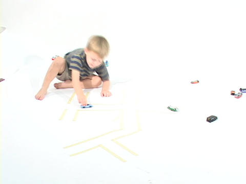 A boy plays with toy cars in a white room Footage
