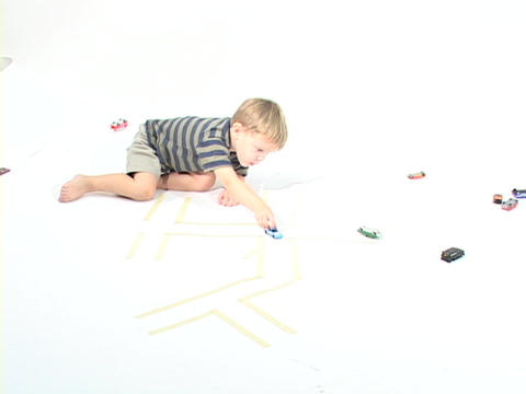 A boy plays with toy cars in a white room Stock Video Footage