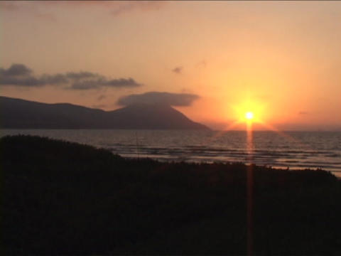 The sun sets near an ocean Stock Video Footage