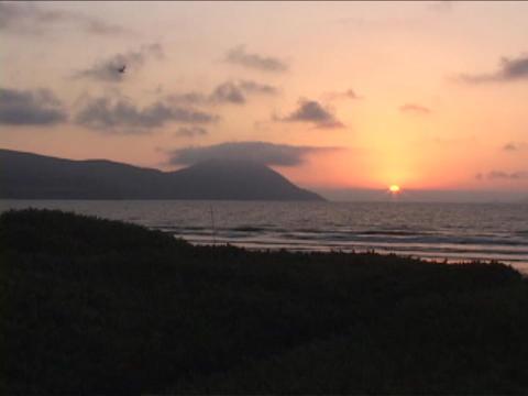 The sun sets near an ocean Stock Video Footage