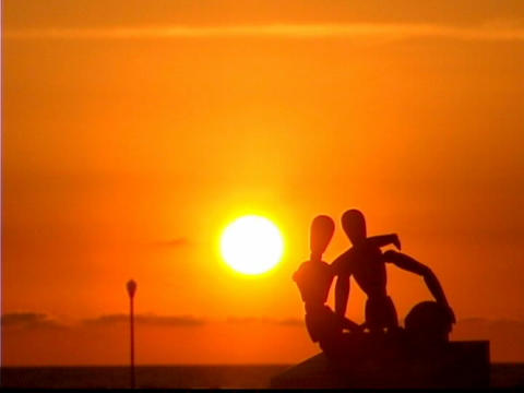 Entwined mannequins sit by the ocean during golden-hour Stock Video Footage