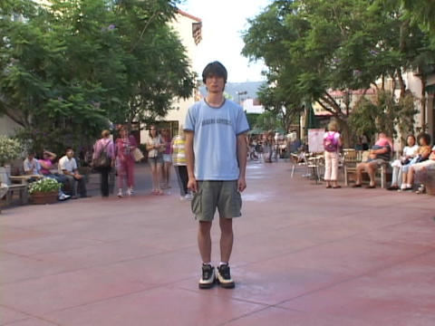 A man stands still in the middle of pedestrians walking through a city park Footage