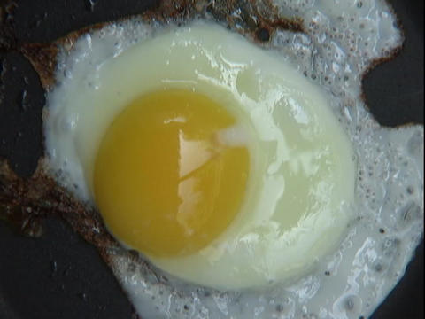 An egg fries in a pan Stock Video Footage