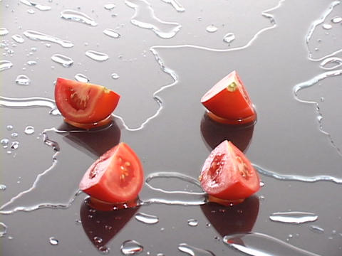 Fresh tomato wedges rest on a wet surface Footage