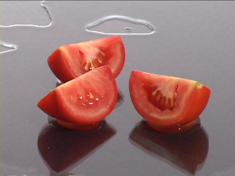Fresh ripe tomatoes rest on a wet surface Stock Video Footage