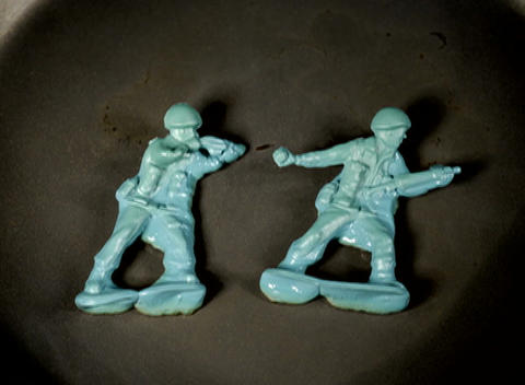Green plastic soldier figures melt Footage
