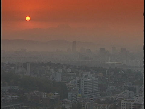 A vivid sun shines through dense fog over a large city Footage