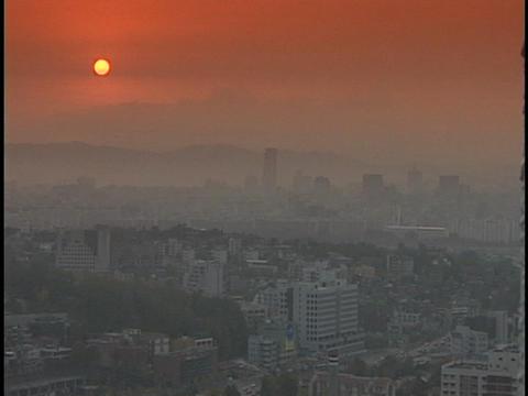 A vivid sun shines through dense fog over a large city Stock Video Footage
