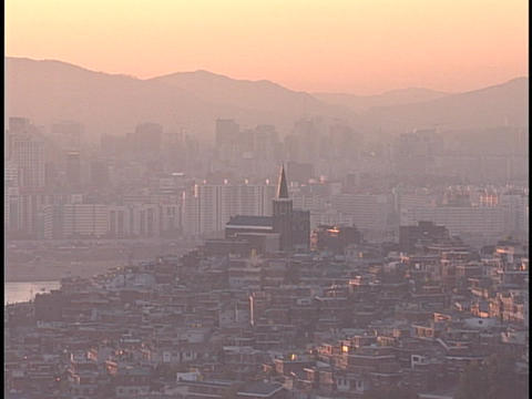 The sun shines through a hazy sky over a crowded city neighborhood Footage