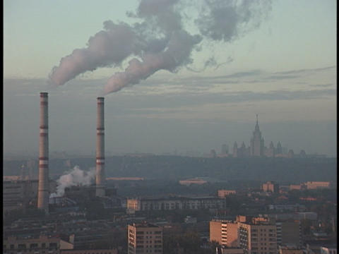 Smoke from two tall smokestacks rises into the sky Footage
