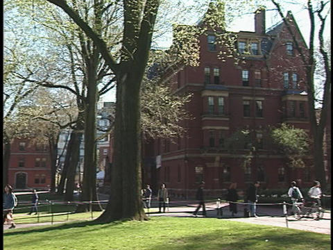 A student strolls across the courtyard at Harvard University Stock Video Footage