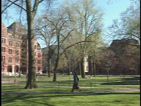 A student strolls across the courtyard at Harvard University Footage