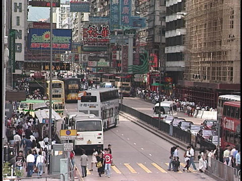 Pedestrians cross a busy intersection Stock Video Footage