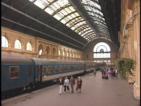 People walk on the platform of a train station Stock Video Footage