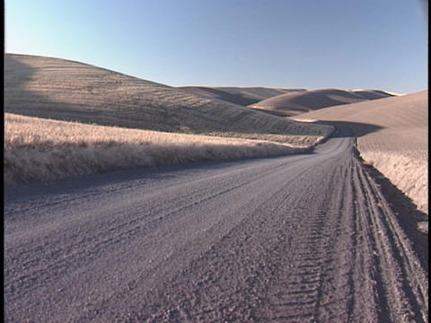 A lonely dirt road follows rolling hills into the horizon Stock Video Footage