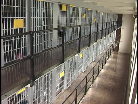stories of jail cells line the walls of a prison block Stock Video Footage