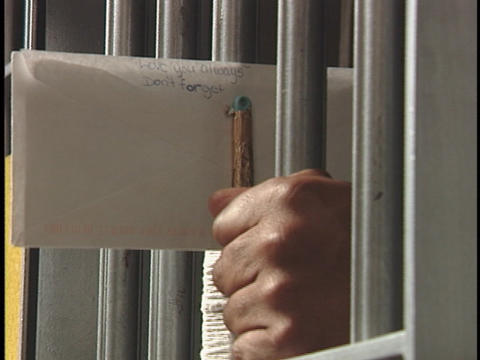 A prisoner places a letter between the bars on his prison-cell Footage