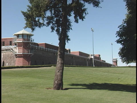 A wall and guard tower surround a correctional facility Stock Video Footage