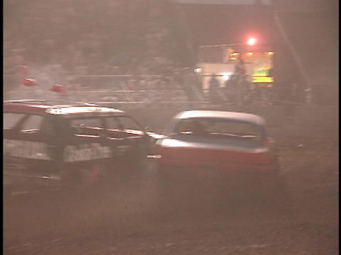 demolition cars smash into each other as they race around a track in an outdoor arena Live Action