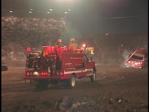 A fire truck enters the arena at a demolition derby Stock Video Footage