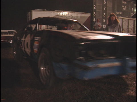 Competitors in a demolition derby drive their cars into an outdoor arena to begin a race Footage
