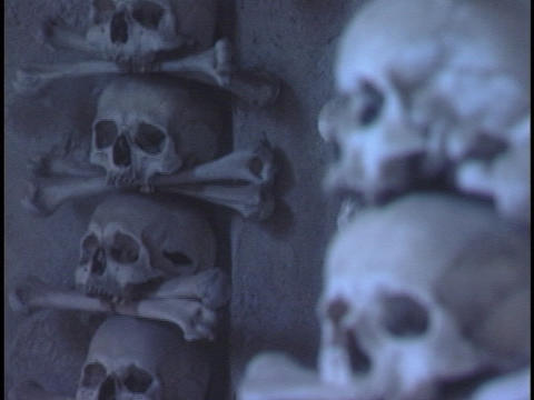 Human skulls and bones are piled high in a catacomb Footage