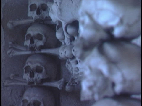 Human skulls and bones are piled high in a catacomb Stock Video Footage