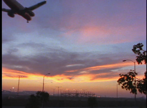 A passenger jet lands on a runway during golden hour Stock Video Footage
