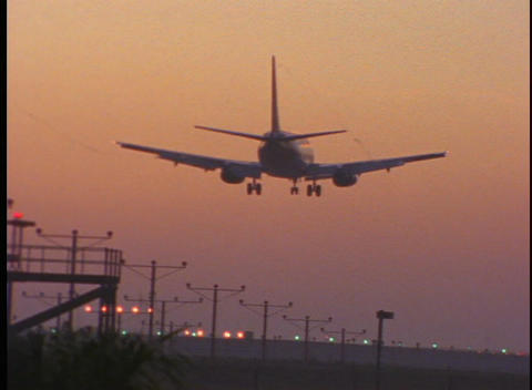 A passenger jet lands on a runway during golden hour Live Action