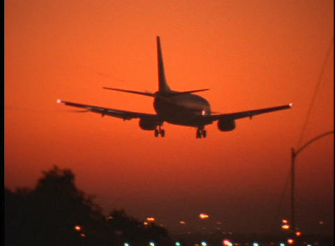 A passenger jet lands on a runway during golden hour Footage