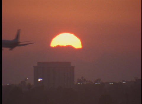 An airplane flies past the sun Stock Video Footage