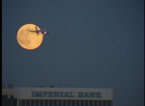 A plane lands against a full moon Stock Video Footage