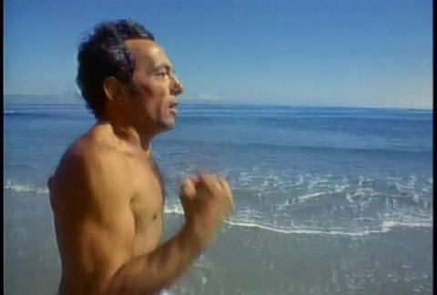 A man jogs along a beach in slow motion Stock Video Footage