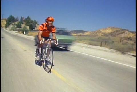 A man on a racing bike pedals along a desert highw Stock Video Footage
