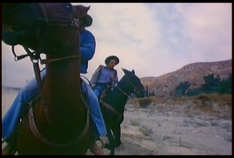 Cowboys ride their horses fast across the desert i Stock Video Footage