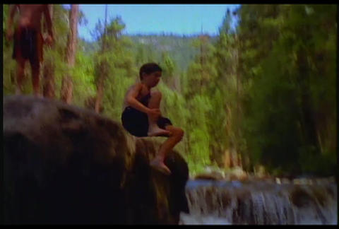 A boy dives into a watering hole Stock Video Footage