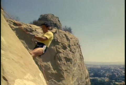 A man rappels down a mountain Stock Video Footage
